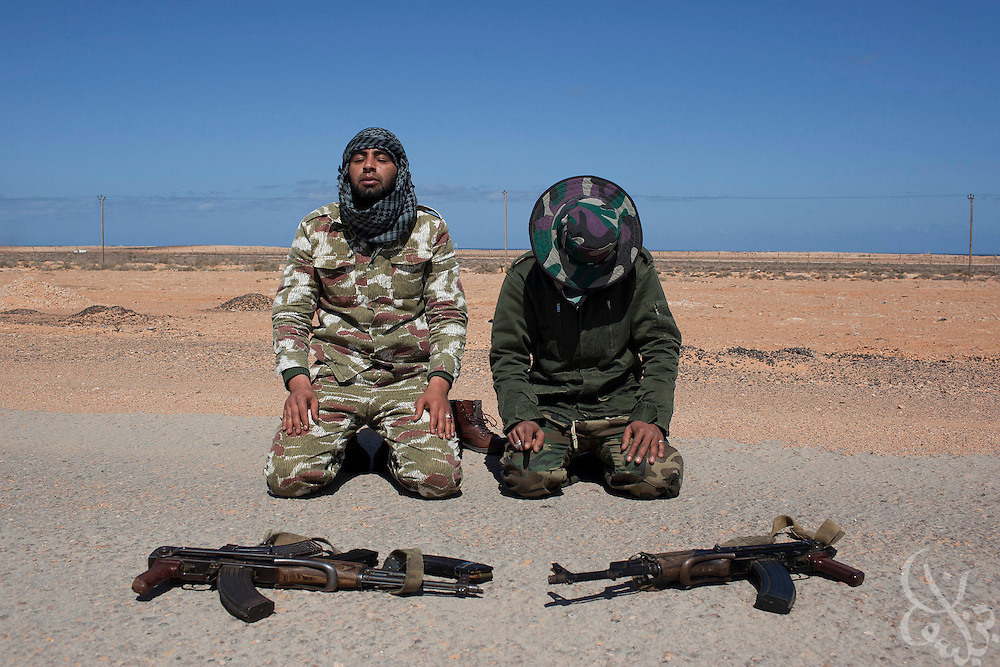 Libyan rebel fighters pray at their position during a day long battle with pro-Qaddafi forces just outside the coastal town of Bin Jawwad. Rebels fought pro-Qaddafi forces there throughout the day as they tried to regain control the town from government forces that seized the town overnight.
