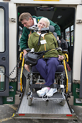 Driver helping wheel chair user up ramp into mini bus,