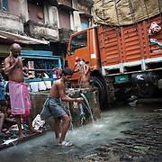 Truck drivers going about their morning duties at Kolkata's fruit market