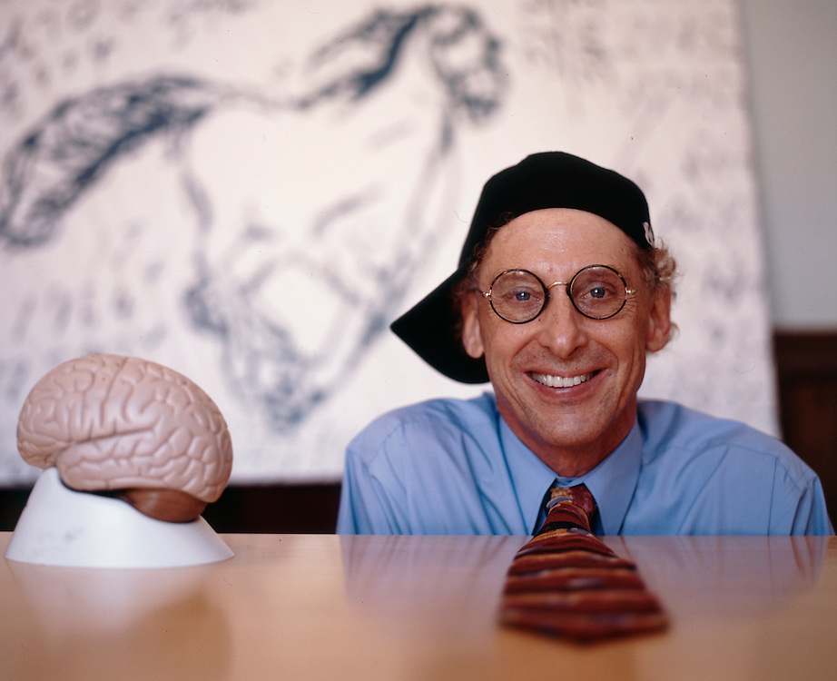 "Professor Alan Snyder of The Centre for the Mind at Sydney University with his ""think cap"". The pictures on the wall were drawn by four year old autistic children...........Sydney, March 2003"