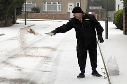 © Licensed to London News Pictures. 18/01/2013.Local resident spreading salt on his road..Snow fall in the borough of Bromley, South East London over night..Snow in Bromley and across the UK today (18.01.13) as  temperatures stay low..Photo credit : Grant Falvey/LNP