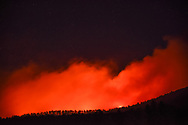 Flames and hot coals on the ground beyond the forested ridge light up the smoke from the Cajete Fire at night, © 2017 David A. Ponton