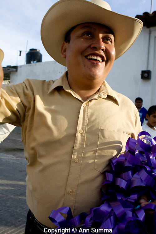 "Juchitan, Mexico: A ""regala,"" or parade, is held by the muxe group ""Baila Conmigo"" the day after the ball. The muxe dress in traditional Tejuana dress and parade through the street with the queen, from whose float are thrown gifts for passersby. Once this was fruit and flowers; now it's tupperware. Carts pulled by oxen and participants on horseback also throw gifts to watchers. Dec. 29, 2008.(photo: Ann Summa)."