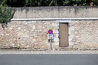 No parking sign against stone wall