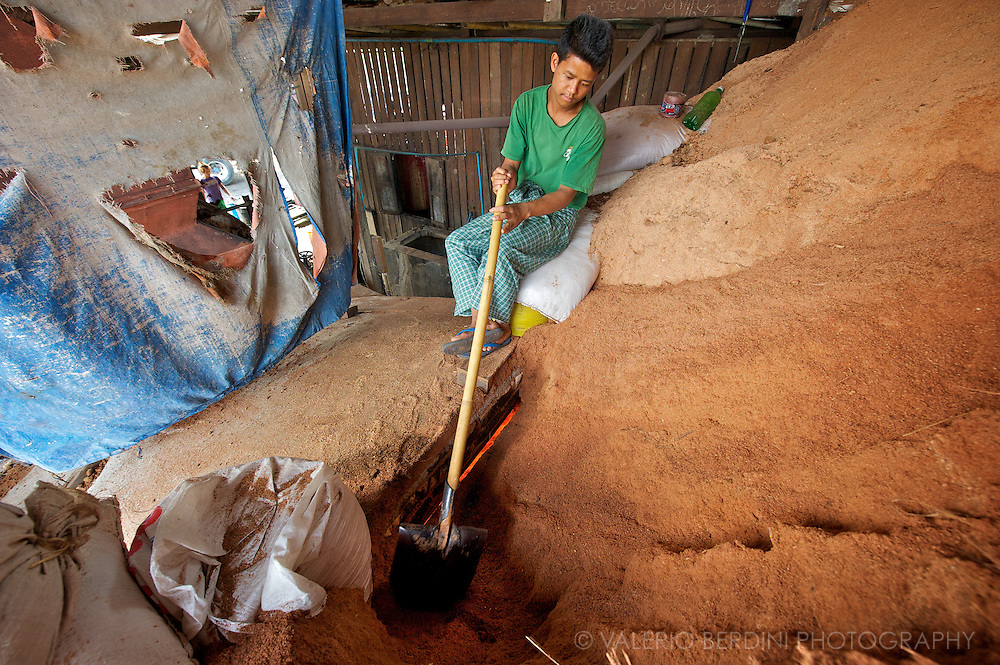 A worker stokes the fire adding sawdust to the kiln.