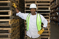 Man standing near wooden pallets in distribution warehouse portrait