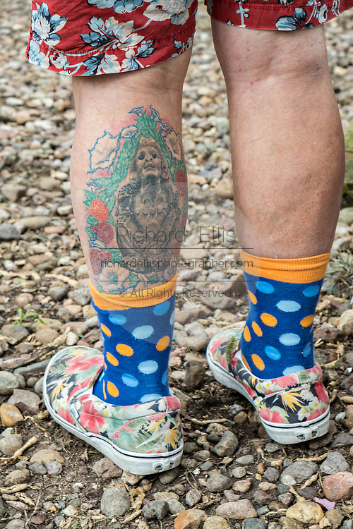 A tattoo on the leg of American artist Anado McLauchlin outside the Chapel of Jimmy Ray in his art compound Casa las Ranas September 28, 2017 in La Cieneguita, Mexico.