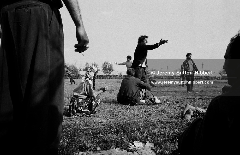THE ANNUAL FOOTBALL GAME DESCENDS INTO ARGUMENT. ROMANIAN ORTHODOX EASTER CELEBRATIONS. SINTESTI, ROMANIA, EASTER 1995. The annual football game descends into argument between the Kalderash Roma men of Sintesti camp, near Bucharest. THe game is poart of their Romanian Orthodox Easter celebrations, the most important in their calendar.