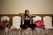 "YANGON,MYANMAR,MARCH 2012: Kimmi stretching up in the dressing room before the concert.<br /> Burma is a country in Transition. And if that hasn't been made clear enough by the political debates and the recent by-elections, meet the Me N Ma Girls, the first girlband in the country.<br /> The timing couldn't be better. After the April 1st elections in 2012 an always increasing number of investors from all over the world has been visiting Myanmar. After decades of military regime and isolation, the strings of censorship have started loosening up. The government censors in fact for years have banned songs and articles, deleting anything that was seen as ""to provocative"" such as leather outfits and colored wigs.<br /> Describing themselves as Myanmar's first all-girl group, under the management of the Australian dancer and choreographer Nicole May, these five women - coming from either Buddhist or Catholic background and formerly known as Tiger Girls - not only have been challenging censorship laws but they're as well trying to win hearts in a society that in many ways remains man-dominated and socially conservative.<br /> In a country that has been locked up for years, the Me N Ma Girls, embracing western pop culture with skimpy outfits and catchy songs, show with every performance the will of the Burmese youth to come out of a decades-long isolation.<br /> Five girls leading a new form of rebellion: the kind that questions roles and cultural norms."