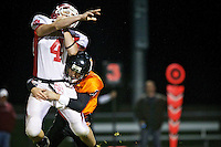 Post Falls High's Tyler Booth puts a hit on Sandpoint's quarterback Ben Schmid during the first half of the Trojan's win Friday over the Bulldogs.