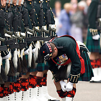 Edinburgh Black Watch troops at inspection before a ceremony. The men wear ceremonial dress, with kilt, sporran, spats and diced hose tops. The inspecting officer is arranging his diced hose tops.