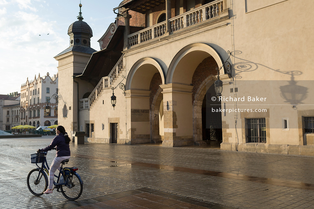 A lady rides her bike past the architecture of the Cloth Hall on Rynek Glowny market square, on 23rd September 2019, in Krakow, Malopolska, Poland.
