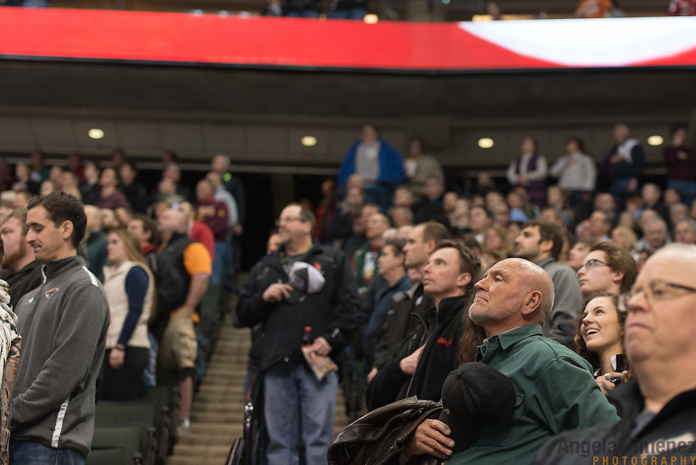 Fans stand for the national anthem at the start of the Class AA semifinal game between Duluth East and Edina (Duluth East won 3-1)at the Minnesota State High School League Boys' State Hockey Tournament at the Xcel Energy Center in St. Paul, Minnesota on March 6, 2015. <br />  <br /> <br /> Photo by Angela Jimenez for Minnesota Public Radio www.angelajimenezphotography.com