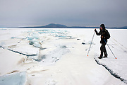 Heleen probes at an ice crack on the first day of her trek across frozen Lake Baikal in Siberia, Russia. .They are a group of five people: Justin Jin (Chinese-British), Heleen van Geest (Dutch), Nastya and Misha Martynov (Russian) and their Russian guide Arkady. .They pulled their sledges 80 km across the world's deepest lake, taking a break on Olkhon Island. They slept two nights on the ice in -15c. .Baikal, the world's largest lake by volume, contains one-fifth of the earth's fresh water and plunges to a depth of 1,637 metres..The lake is frozen from November to April, allowing people to cross by cars and lorries.