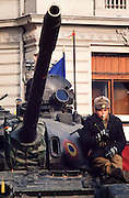 December 26, 1989. Bucharest, Rumania. A soldier sitting on his Soviet-built T-54 tank with a flower helps guarding the revolution. (Photo Heimo Aga)