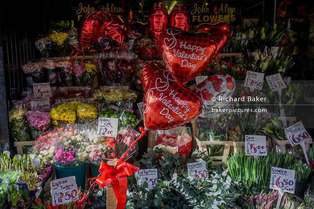 Valentine's Day balloons sold next to bouquets display in London florists.