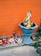 A shrine with offerings of food and soda on a side street.