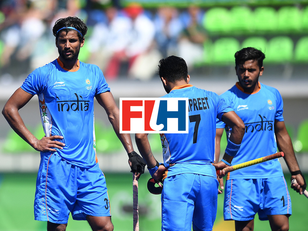 India's Rupinder Pal Singh  (L) looks on during the men's field hockey Netherland's vs India match of the Rio 2016 Olympics Games at the Olympic Hockey Centre in Rio de Janeiro on August, 11 2016. / AFP / MANAN VATSYAYANA        (Photo credit should read MANAN VATSYAYANA/AFP/Getty Images)