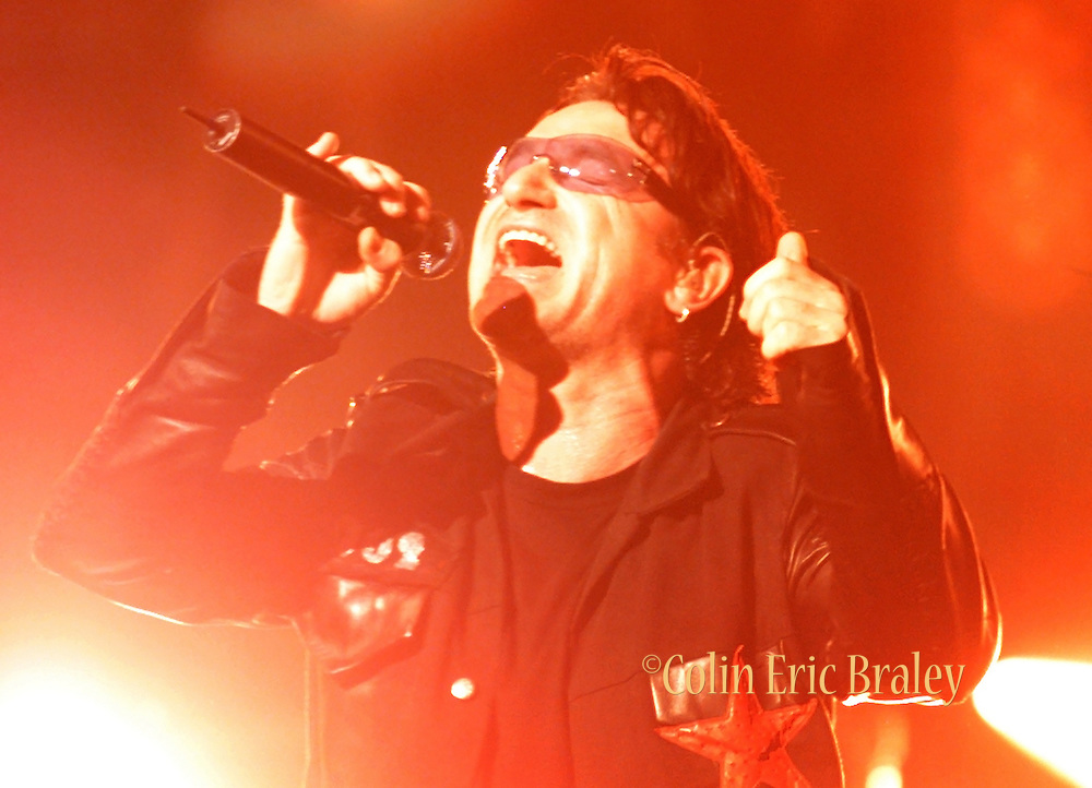 Basking in the red stage lights, Bono of U2 sings Sunday Bloody Sunday, during the rock groups performance at American Airlines Arena in Miami.