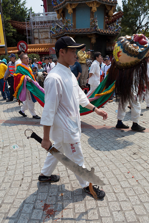 A young man carries a blade weapon during a ceremony to mark the birthday of the Bao Sheng Emperor on the 14th day of the 3rd lunar month in the Chinese calendar.