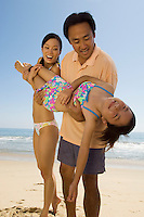 Parents Playfully Carrying Daughter on Beach