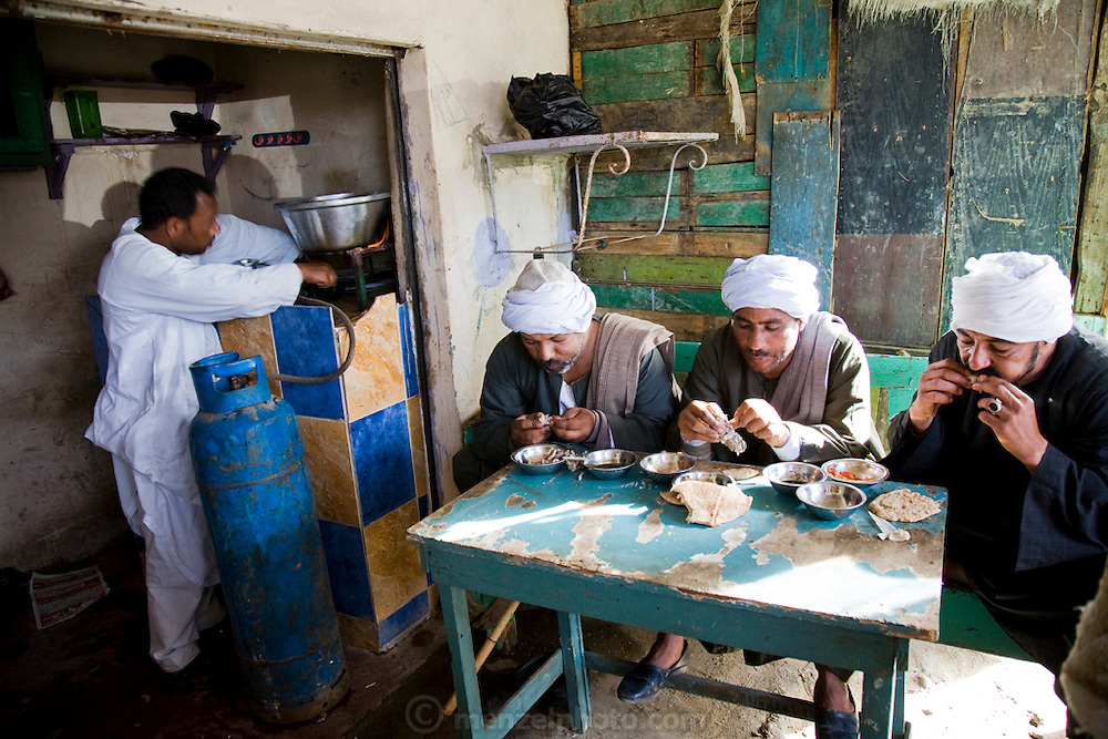 Truck drivers enjoy a mid-morning meal of sheep meat, potato, onion, tomato, and flat bread in a rustic restaurant stall at the Birqash Camel Market outside Cairo, Egypt, where Saleh Abdul Fadlallah works as a broker. (Abdul Fadlallah is featured in the book What I Eat: Around the World in 80 Diets.)