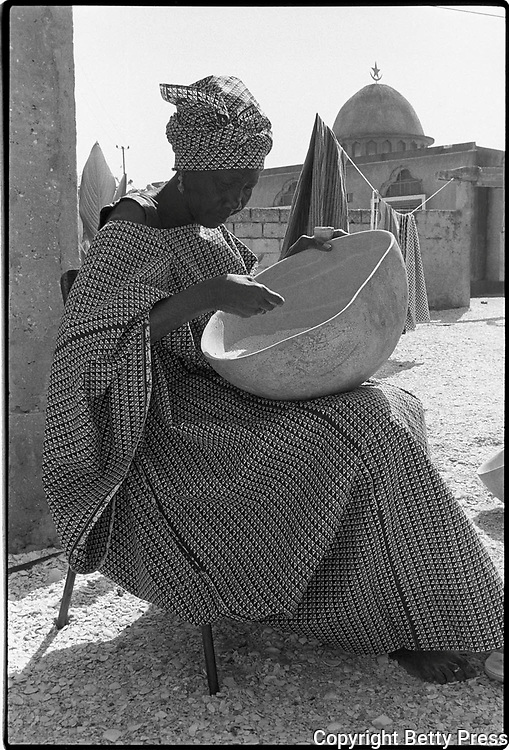 A calabash with holes cannot be filled. Kenyan proverb<br /> <br /> While visiting a women&rsquo;s group that was setting up a dried fish business, I saw this woman sitting in a courtyard cleaning rice. As she was doing this most mundane job, she was beautifully dressed and so composed that even having her picture taken did not distract her from her work. Cleaning rice, Mbao, Senegal  1988