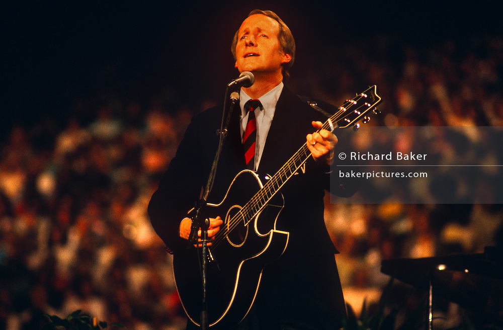 Country and Western singer George Hamilton IV performs in front of British Christians during Mission 89, a series of evangelical revival rallies in London, England held by Baptist Christian Billy Graham. Hamilton is a Singer/guitarist/songwriter of country, rock, folk, Christian and gospel songs with 40 on Billboard's country music charts in 1960s and '70s. He is a member of the Grand Ole Opry with best-sellers like Abilene and A Rose And A Baby Ruth. George has been a frequent guest singer with the Dr. Billy Graham Crusades such as this in 1989.