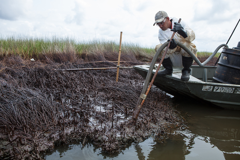 August, 8, 2010,  BP clean-up crew worker vacuumes BP Oil on the surface of the water in Bay Jimmy  and in the marsh where the  BP oil spill had the greatest impact in Plaquemines Parish.