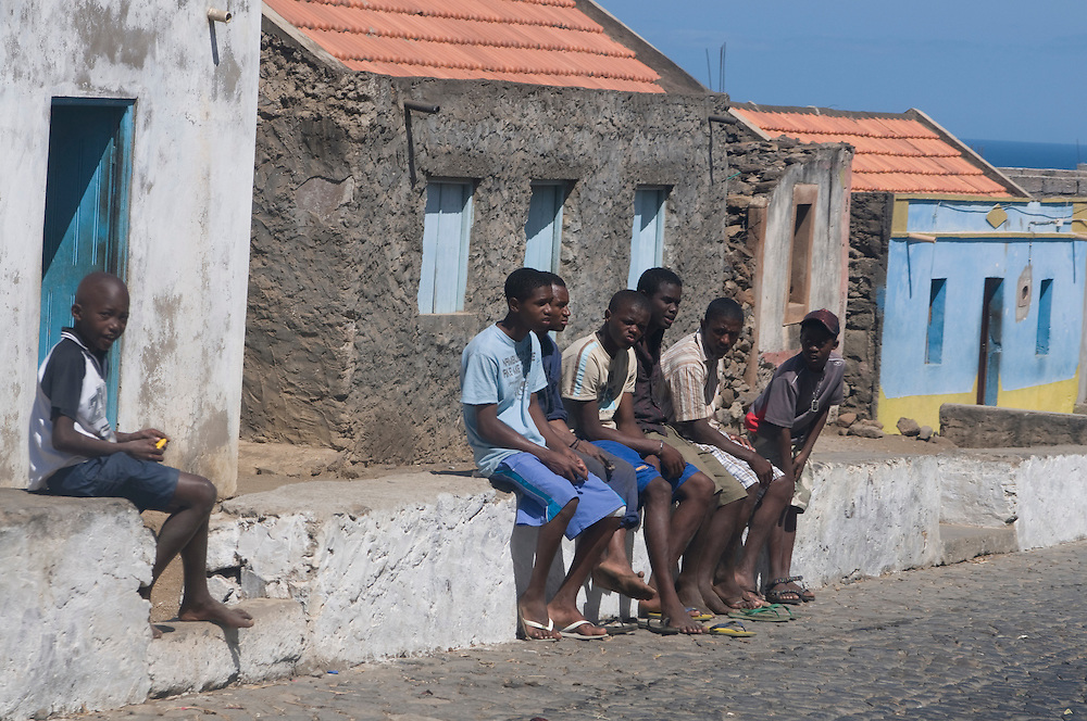 Dark skinned, young men, sitting on wall. Santiago. Cabo Verde. Africa.