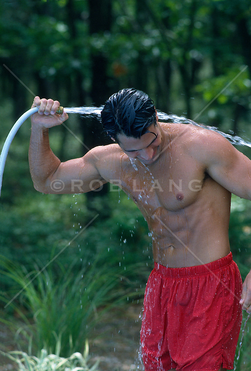 muscular man hosing himself down outdoors