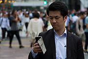 A Japanese salaryman or male office worker, checks his smart phone in Hachiko Square, Shibuya, Tokyo, Japan Tuesday June 27th 2017