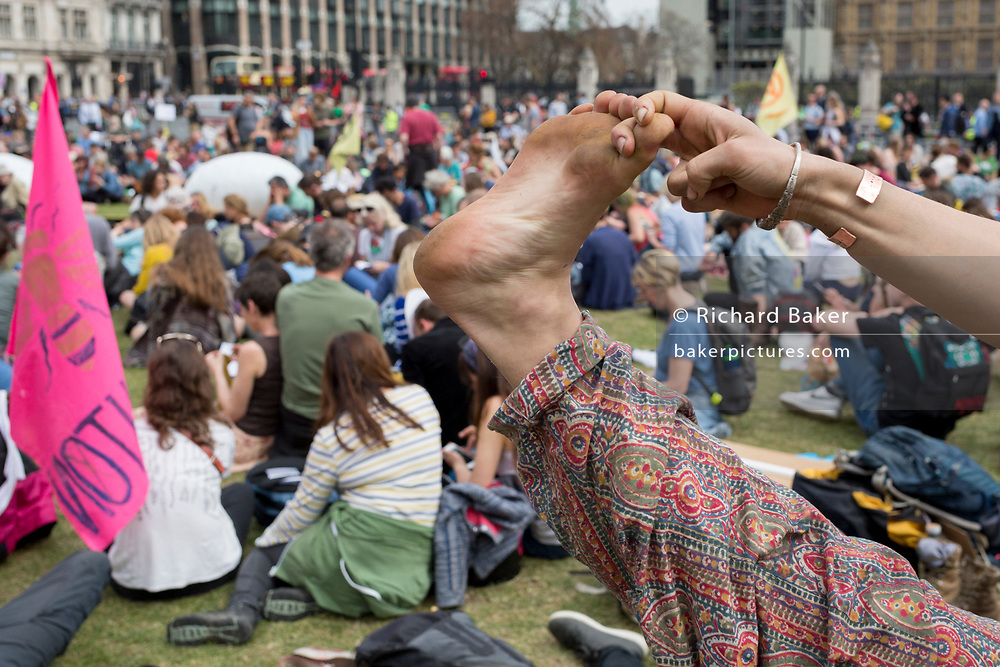 An activist makes a yoga stretch in Parliament Square during the week-long protest by climate change activists with Extinction Rebellion's campaign to block road junctions and bridges around the capital, on 23rd April 2019, in London England.
