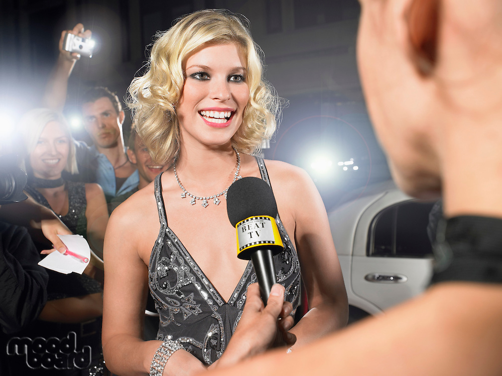 Woman talking into microphone on red carpet