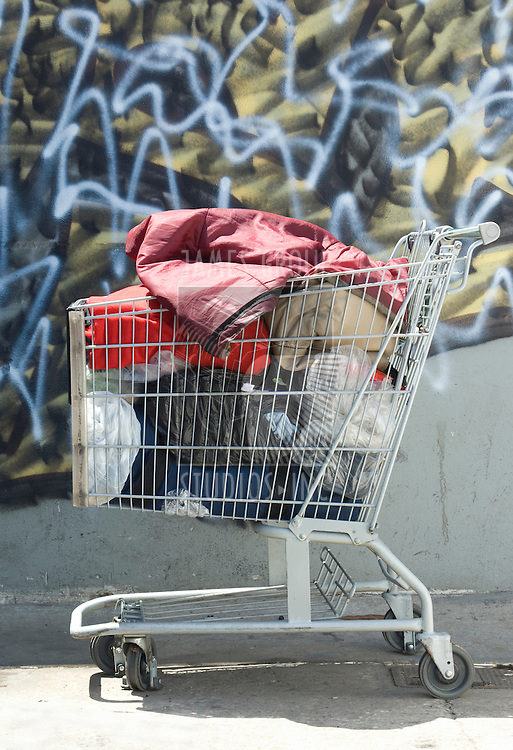 Shopping cart appropriated by a homeless person against a graffiti backdrop