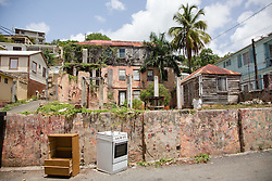 Illegally disposed appliances and furniture litter the current site of what used to be the Catholic Hospital which was charged with treating Savan residents in its time.  The Virgin Islands Economic Development Association Enterprise & Commercial Zone Commission hosts a historical tour through the Savan (Savanne) neighborhood.   St. Thomas, US Virgin Islands.  9 July 2015.  © Aisha-Zakiya Boyd