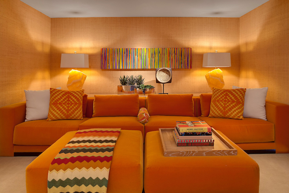 Brightly decorated TV/sitting room with burnt orange velvet couches and ottomans. Lamps are made from orange and white quartz. Mid century modern home, Palm Springs, CA