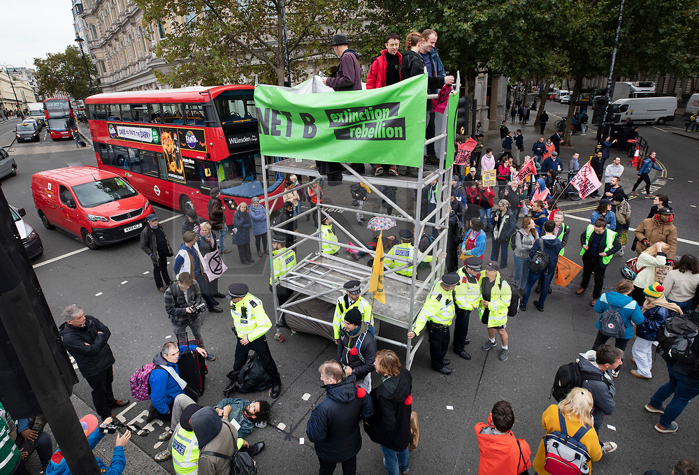 © Licensed to London News Pictures. 07/10/2019. London, UK. Extinction Rebellion activists blockade Trafalgar Square, central London with a scaffolding tower. Activists are converging on Westminster blockading roads in the area for at least two weeks calling on government departments to 'Tell the Truth' about what they are doing to tackle the Emergency. Photo credit: Peter Macdiarmid/LNP