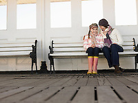 Mother and daughter sitting together on pier bench low angle view