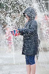 © Licensed to London News Pictures. 03/06/2012}. Bristol, Uk. A child plays in the fountains in Millennium Square, Bristol, during the screening of the pageant as part of the the Royal Jubilee celebrations. Great Britain is celebrating the 60th  anniversary of the countries Monarch HRH Queen Elizabeth II accession to the throne this weekend Photo credit :David mirzoeff/ LNP