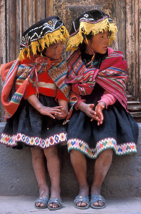Pisaq Indian sisters sitting in an old doorway in Cuzco, Peru