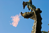 fire comes out of the mouth of the wawel dragon in this close up shot of the dragon's head. bright blue sky in the background