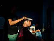 "14 FEBRUARY 2019 - SIHANOUKVILLE, CAMBODIA:  A Chinese man who works in a casino gets a haircut at a Chinese barbershop in Sihanoukville. There are thousands of Chinese workers in Sihanoukville who work to support the casino and hotel industry in the town and thousands of other Chinese migrants have moved into Sihanoukville and opened businesses that cater to the workers. There are about 80 Chinese casinos and resort hotels open in Sihanoukville and dozens more under construction. The casinos are changing the city, once a sleepy port on Southeast Asia's ""backpacker trail"" into a booming city. The change is coming with a cost though. Many Cambodian residents of Sihanoukville  have lost their homes to make way for the casinos and the jobs are going to Chinese workers, brought in to build casinos and work in the casinos.      PHOTO BY JACK KURTZ"