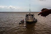 A passenger, unseen, holds his hands as he leans from his boat to look on the movement on a nearby ship navigating the Amazon river in Bailie archipelago, Brazil, Sunday, Oct. 23, 2016. Bathed by the Amazon river mouth  this northernmost capital of 400.000 residents is as filled with canals, informal docks and unregistered boats as it lacks infrastructure and control means for fighting the rising river piracy plaguing passengers and transportation companies. (Dado Galdieri for The New York Times)