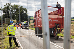 Offchurch, UK. 24th August, 2020. A police officer monitors an anti-HS2 activist who had occupied a trailer transporting wood chip in order to try to prevent or delay tree felling alongside the Fosse Way in connection with the HS2 high-speed rail link. The controversial HS2 infrastructure project is currently expected to cost £106bn and will destroy or significantly impact many irreplaceable natural habitats, including 108 ancient woodlands.