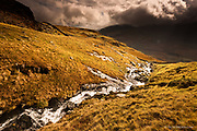 Huge slabs of rock just underneath the grass and peat inclined steeply. A fast flowing stream cuts down into the joint as it tumbles down towards the wide glaciated Ogwen in the distance. Heavy rain clouds hang over some of Snowdonia's highest peaks.