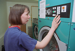 Female hostel resident using drier in communal laundry room of 'shared living cluster',