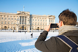 © Licensed to London News Pictures. 28/02/2018. London, UK. A man takes a photograph of Buckingham Palace after heavy overnight snowfall in London as the 'Beast from the East brings freezing Siberian air to the UK. Photo credit: Rob Pinney/LNP