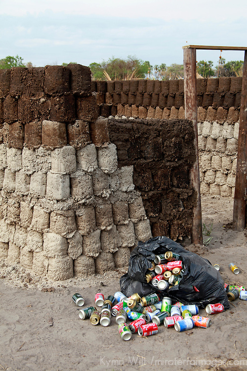 Africa, Botswana, Okavango Delta. Sustainable village homes and structures in the Okavango Delta - recycled cans are used within the dung and mud walls to insulate.