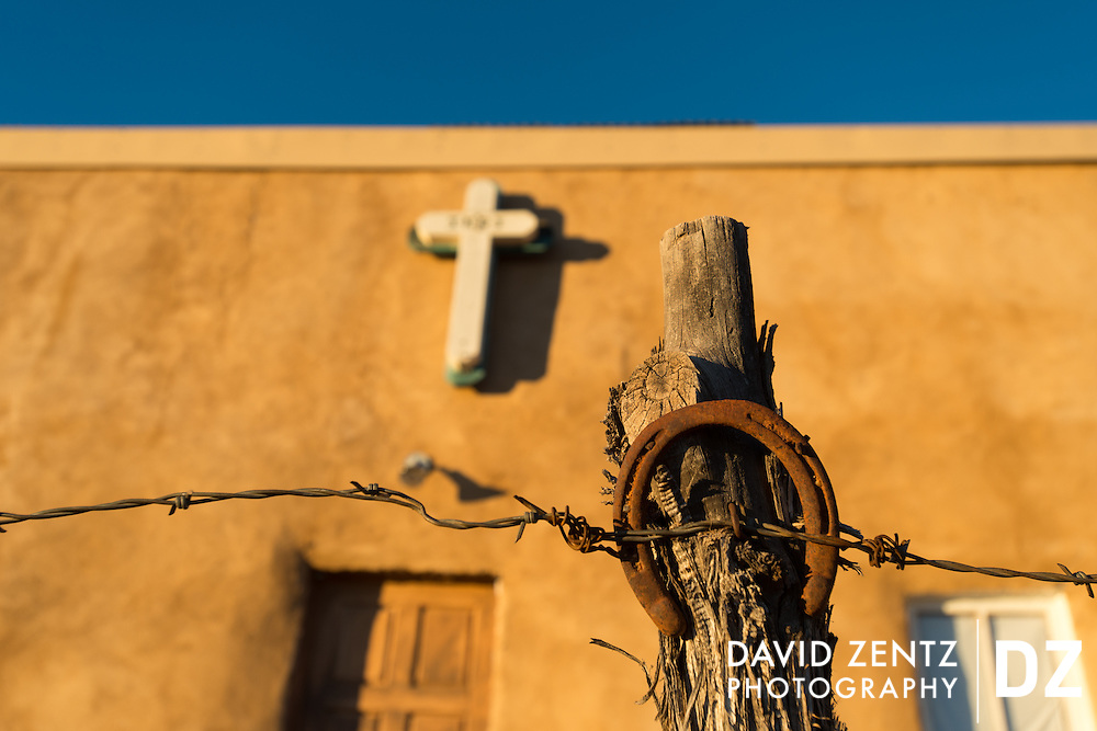 Both symbols of the southwest, a cross and a horseshoe decorate a building in Truchas, New Mexico, on Dec. 24, 2013.